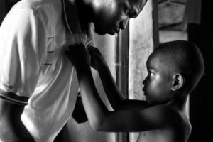 παιδί κουμπώνει το πουκάμισο του πατέρα του