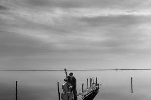 ηλικιωμένος παίζει βιολοντσέλο σε προβλήτα λιμανιού