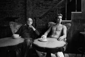 δύο άντρες καθισμένοι σε πολυθρόνες, ο ηλικιωμένος ντυμένος, ο νεος γυμνός