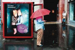 street photography, άντρας κρατάει κόκκινη ομπρέλα μπροστα από αφίσα που δείχνει ζευγάρι με σακούλες στα κεφάλια