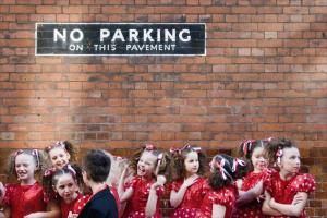 πινακίδα no parking, κορίτσια ντυμένα στα κόκκινα και ένα αγοράκι