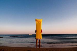 άντρας κρατάει ένα στρώμα θαλάσσης κρύβοντας το σώμα του