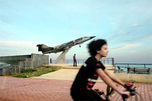 κορίτσι κάνει ποδήλατο, στο φόντο ένα αεροπλάνο