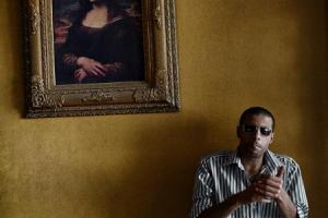 ένας μελαμψός κύριος φοράει γυαλιά και ανάβει πούρο μπροστά στον πίνακα της Gioconda