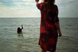 γυναίκα στην παραλία χαιρετά μία άλλη γυναίκα μεσα στη θάλασσα