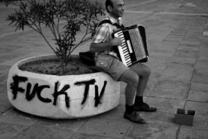 μουσικός με ακορντεόν καθισμένος σε ένα παρτέρι σε κάποια πλατεία