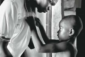 έγχρωμο παιδάκι κουμπώνει το πουκάμισο του πατέρα του