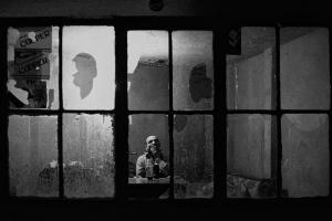 ασπρόμαυρη φωτογραφία, ηλικιωμένος σε κτήριο με σπασμένα παράθυρα