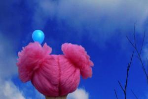 πάνινη κούκλα με ροζ μαλλί κοιτάει ένα γαλάζιο μπαλόνι στον ουρανό