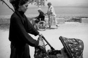 γυναίκα στα ντυμένη στα μαύρα κάνει βόλτα το παιδί της στο καροτσάκι / γυναίκα ντυμένη στα άσπρα κάνει βόλτα τον αντρα της καθισμένο σε αναπηρικό καροτσάκι