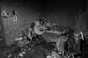 ασπρόμαυρη φωτογραφία ενός άστεγου σε έναν ακατάστατο χώρο
