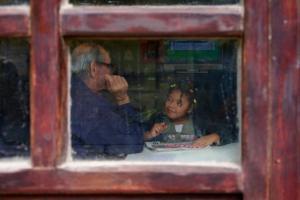 μέσα απο ένα παράθυρο ένας κύριος μιλά με ένα αφροαμερικάνικο κορίτσι που κρατά μία εφημερίδα