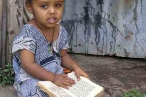μικρό κορίτσι καθισμένο σε σκαλιά με ένα βιβλίο στα πόδια