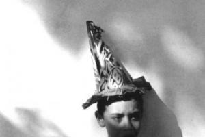 ασπρόμαυρη φωτογραφία, παιδί στέκεται σε τοίχο φορώντας ένα μεγάλο καπέλο