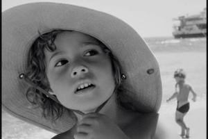 ασπρόμαυρη φωτογραφία, παιδί με ψάθινο καπέλο σε παραλία, πορτραίτο