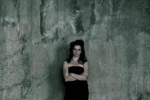 γυναίκα τυλισμένη με μάυρο σεντονι, γκρι τοίχος
