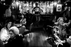 νυχτερινό μαγαζί, κόσμος καθισμένος σε τραπέζια, άντρας παίζει ακορντεόν -- Φωτογραφία: Βασιλικός Λουκάς (1ο βραβείο στην α/μ Φωτογραφία)
