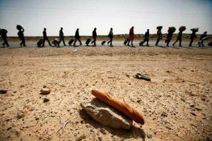 μετανάστες με βαλίτσες στο βάθος, ψωμί πάνω σε πέτρα