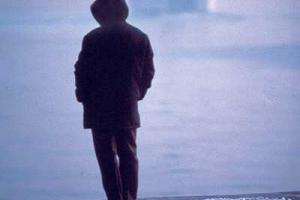 άντρας περιμένει στο λιμάνι, πλοίο στο βάθος
