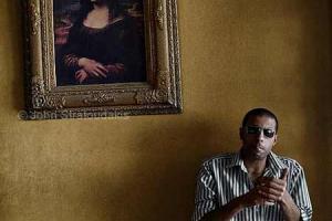 άντρας με γυαλιά και τσιγάρο ποζάρει μπροστά από το πίνακα της Μόνα Λίζα