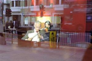 αντανάκλαση από λεωφορείο, νεαρός πίνει καφέ, άντρας κοιτάει έγγραφα