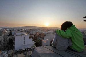 δύο παιδιά αγκαλιασμένα, ανεβασμένα σε κτήριο κοιτάνε το ηλιοβασίλεμα