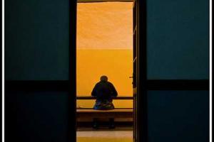 ανοιχτή πόρτα ενός δωματίου, κίτρινο φως, άνδρας που τρώει σε εναν πάγκο