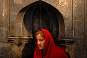 μωαμεθανή γυναίκα με κόκκινη μαντήλα προσεύχεται