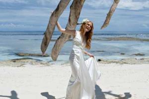 γυναίκα με μακρύ άσπρο φόρεμα ποζάρει σε μία παραλία