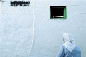 γυναίκα με μαντήλα μπροστά σε ένα κτήριο με ένα μικρό παράθυρο και το όνομα της οδού Χαρίτου Γαβριήλ