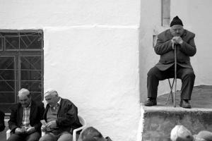 ασπρόμαυρη φωτογραφία / ηλικιωμένοι άνδρες κάθονται / ένας απο αυτούς στηρίζετια σκεφτικός στο μπαστούνι του