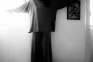 ασπρόμαυρη φωτογραφία / κοπέλα με όρθια πάνω σε κρεβάτι με ανοιχτά τα χέρια