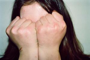 γυναίκα κρύβει το πρόσωπό της με τις δροθιές της