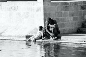 ασπρόμαυρη φωτογραφία, δύο άνδρες καθισμένη σε μια πλατεία, ο ένας έχει τα πόδια στο νερό
