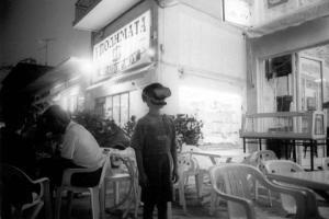 ασπρόμαυρη φωτογραφία, παιδί με μάσκα και γυαλιά στέκεται στη μέση ενός υπάιθριου μαγαζιού, πλαστικές καρέκλες