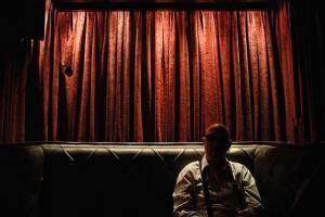 άνδρας καθισμένος σε καναπές, κόκκινη κουρτίνα