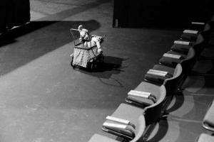 παιδικό καρότσι παιχνίδι μπροστά από μια σειρά θέσεων σε θέατρο