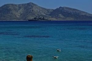 αγόρι κάθεται στο πλακόστροτο με μαγίο και κοιτάει δύο γλάρους στη θάλασσα / στο βάθος ένα καράβι και απο πίσω βουνό
