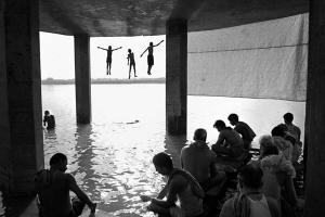 ασπρόμαυρη φωτογραφία, άνθρωποι σε υπόστεγο, νερό, παιδιά χωροπηδάνε στον αέρα