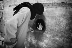 ασπρόμαυρη φωτογραφία, γυναίκα με μαντήλα, χέρι μεσα σε τρύπα, τοίχος