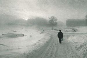 μαυροφορεμένος άνθρωπος περπατά σε ένα χιονισμένο τοπίο