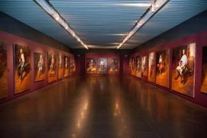 Χώρος έκθεσης με κρεμασμένους πίνακες πορτρέτων