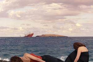 παραλία Κυθήρων και δύο γυναίκες με ναυάγιο στο βάθος -- φωτογραφία: Nicki Upstairs