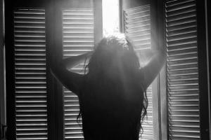 ασπρόμαυρη φωτογραφία / κοπέλα στέκεται μπροστά σε παράθυρο με μισάνοιχτα παντζούρια απο τα οποία περνάνε μέσα ηλιαχτίδες