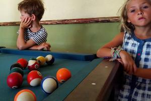 ένα αγόρι κι ένα κορίτσι ακουμπούν πάνω σε ένα μπιλιάρδο