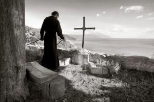 μοναχός στο άγιο όρος πίσω απο έναν σταυρό με θέα την θάλασσα