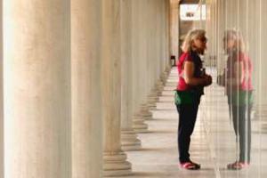 γυναίκα στην είσοδο αρχαιολογικού χώρου κοιτά την αντανάκλαση της στη τζαμαρία