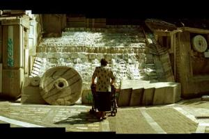 ηλικιωμένη γυναίκα με καροτσάκι διδύμων μπροστά από το συντριβάνι Λάρισας
