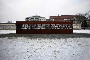 κομμάτι απο το Τείχος του Βερολίνου με φωτογραφίες ανθρώπων επάνω / χιονισμένο τοπίο