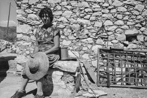 γυναίκα της Μάνης καθισμένη σε πέτρινο πεζούλι